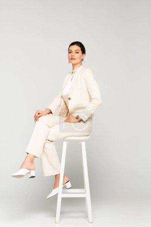 attractive confident businesswoman in white suit sitting on stool, on grey
