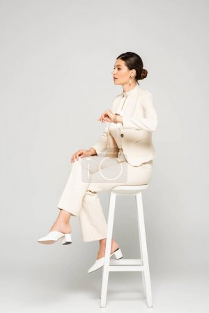 elegant businesswoman in white suit sitting on stool, on grey