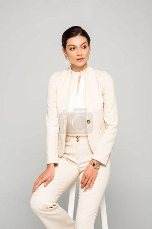 Photo pour Élégante femme d'affaires en costume blanc assise sur tabouret, isolée sur gris - image libre de droit