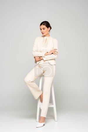 elegant confident businesswoman in white suit sitting on stool, on grey