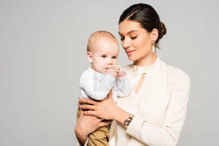 Photo pour Attrayant femme d'affaires tenant bébé garçon sur les mains, isolé sur gris - image libre de droit