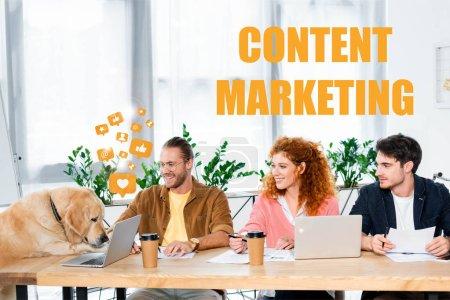 Photo pour Trois amis souriant et regardant une jolie golden retriever au bureau avec une illustration de marketing de contenu - image libre de droit