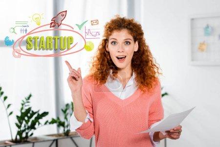 Foto de Una mujer de negocios atractiva y conmocionada que muestra el signo de la idea y sostiene el papel con ilustración inicial. - Imagen libre de derechos