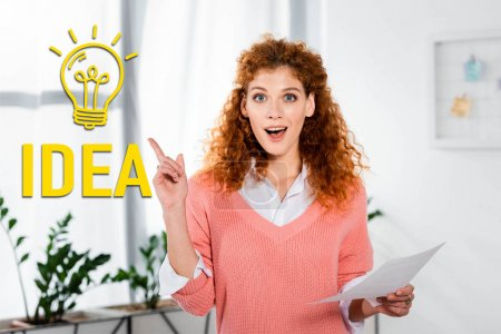 Photo for Attractive and shocked businesswoman showing idea sign and holding paper near light bulb illustration - Royalty Free Image
