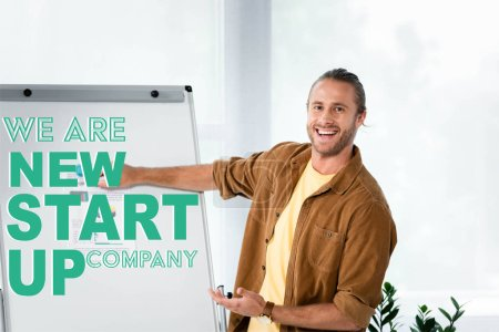 Photo for Handsome and smiling businessman pointing at flipchart with we are new startup company illustration - Royalty Free Image