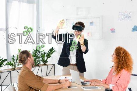 """Photo pour Un homme d'affaires souriant avec son casque d """"écoute vr se tenant au bureau près de collègues et une illustration de démarrage - image libre de droit"""
