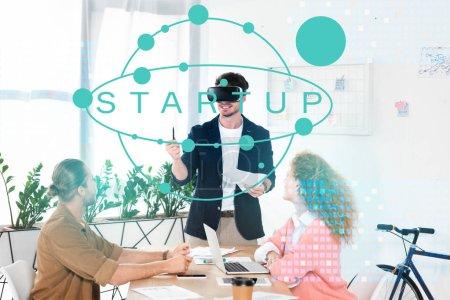 Photo pour Homme d'affaires souriant avec son casque d'écoute vr en fonction près de collègues et illustration de démarrage - image libre de droit