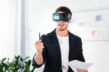 Photo for Businessman in shirt with virtual reality headset with cyber security illustration holding pen and papers - Royalty Free Image