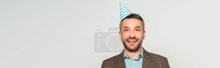 Panoramaaufnahme eines glücklichen Mannes mit Partymütze, der isoliert auf graue Kamera blickt