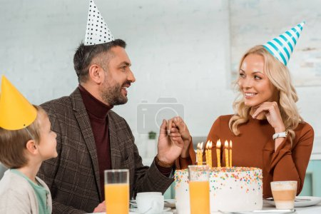 Photo pour Homme et femme heureux tenant la main tout en étant assis à table avec fils près du gâteau d'anniversaire avec des bougies allumées - image libre de droit