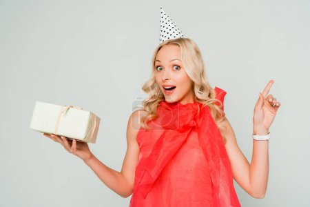 surprised woman looking at camera while holding gift box and pointing with finger isolated on grey