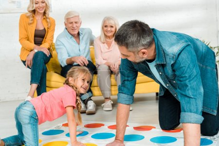 Photo pour Kyiv, Ukraine - November 21, 2019 : cheerful father and daughter playing twister game near family sitting on sofa - image libre de droit