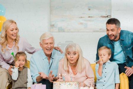 Foto de Mujer mayor que sopla velas en tarta de cumpleaños mientras se sienta en un sofá cerca de una familia feliz. - Imagen libre de derechos