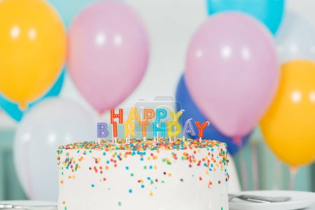 Foto de Delicioso pastel de cumpleaños con velas y carta de cumpleaños feliz cerca de coloridos globos festivos. - Imagen libre de derechos