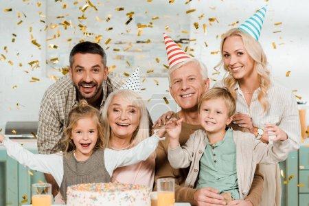 Foto de Feliz familia sentada bajo la caída de confetti cerca del pastel de cumpleaños y sonriendo a cámara - Imagen libre de derechos