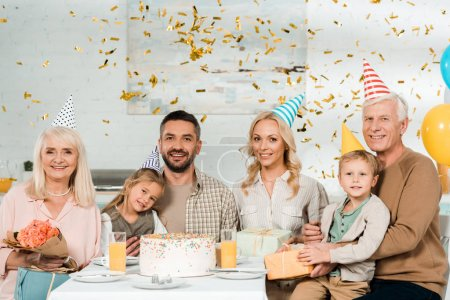 Photo for Cheerful family sitting at kitchen table near birthday cake under falling confetti and smiling at camera - Royalty Free Image