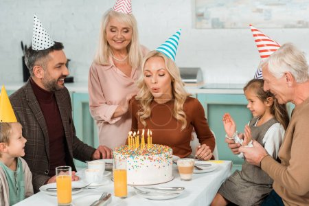 Foto de Mujer feliz soplando velas encendidas en tarta de cumpleaños cerca de la familia sentada en la mesa de cocina - Imagen libre de derechos