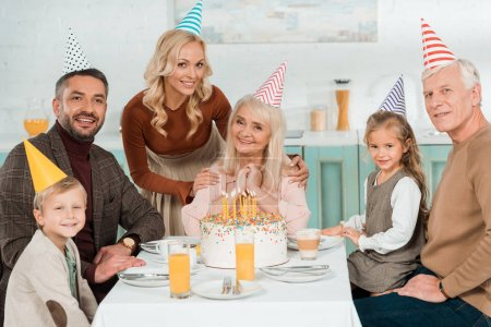 Photo pour Femme souriante touchant les épaules de la femme âgée heureuse tandis que toute la famille assise près du gâteau d'anniversaire - image libre de droit