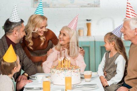 Foto de Mujeres sonrientes que tocan hombros de mujeres mayores felices mientras toda la familia se sienta cerca del pastel de cumpleaños. - Imagen libre de derechos