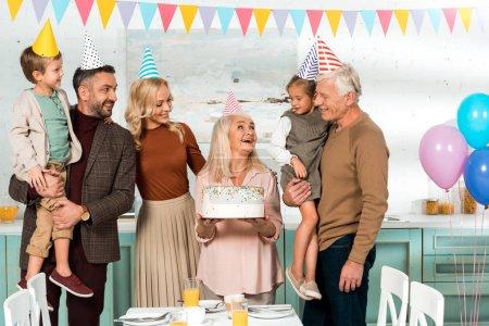 Foto de Feliz mujer mayor que celebra tarta de cumpleaños cerca de la familia alegre en los sombreros de fiesta - Imagen libre de derechos