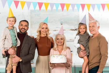 Foto de Feliz mujer mayor que celebra tarta de cumpleaños cerca de la familia en los sombreros de fiesta sonriendo a cámara. - Imagen libre de derechos
