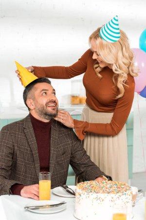 Photo pour Femme souriante mettant casquette de fête sur mari heureux assis à la table avec gâteau d'anniversaire - image libre de droit