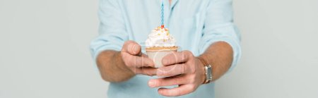 Photo for Cropped view of senior man in party cap holding birthday cupcake isolated on grey, panoramic shot - Royalty Free Image