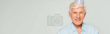 Photo pour Plan panoramique de heureux homme âgé en bonnet de fête souriant à la caméra isolé sur gris - image libre de droit