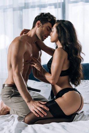 Photo pour Homme sans chemise en pantalon et femme en lingerie noire et bas s'embrassant sur le lit - image libre de droit