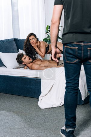 Photo pour Femme choquée avec son amant regardant mari debout dans la chambre - image libre de droit