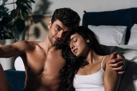 Photo for Happy, sexy man looking at camera while hugging beautiful girlfriend in bed - Royalty Free Image