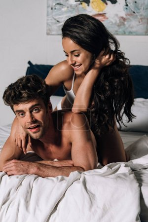 Photo for Cheerful man looking at camera while lying on bed with happy girlfriend - Royalty Free Image