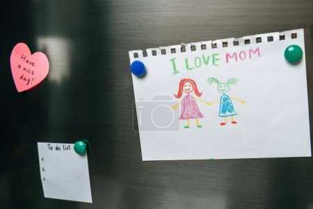 Photo for Close up view of notes and drawing on fridge door - Royalty Free Image