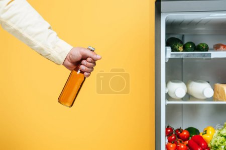 Photo pour Cropped view of man holding bottle of beer near open fridge with fresh food on shelves isolated on yellow - image libre de droit