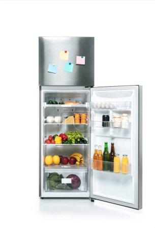 Photo pour Réfrigérateur ouvert avec aliments frais sur les tablettes et billets collants vierges isolés sur blanc - image libre de droit