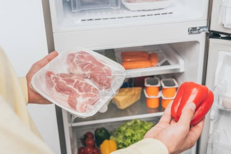 Photo for Cropped view of man holding frozen meat and fresh bell pepper near open fridge full of food - Royalty Free Image