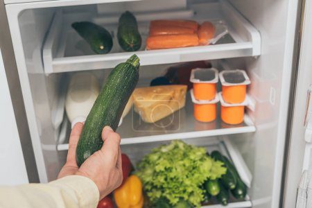 Photo for Cropped view of man holding cucumber near open fridge full of food - Royalty Free Image