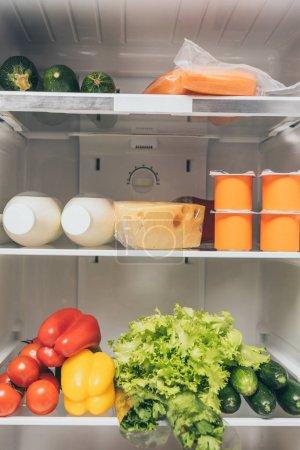 Photo pour Open fridge full of fresh food on shelves - image libre de droit