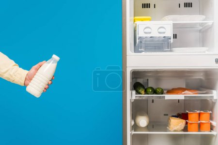 Photo for Cropped view of man holding milk near open fridge and freezer with fresh food on shelves isolated on blue - Royalty Free Image