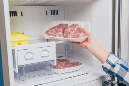 Foto de Cropped view of woman taking out frozen meat from freezer - Imagen libre de derechos