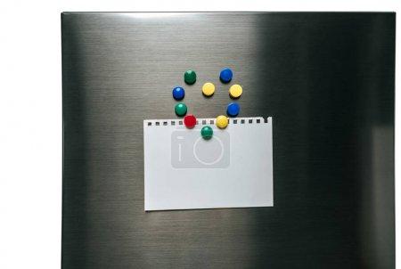 Photo pour Papier vide suspendu au réfrigérateur en acier inoxydable avec aimants disposés en coeur isolé sur blanc - image libre de droit
