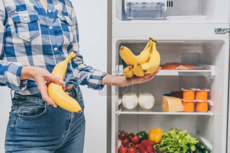 Photo for Cropped view of woman holding bananas near open fridge with fresh food on shelves isolated on white - Royalty Free Image
