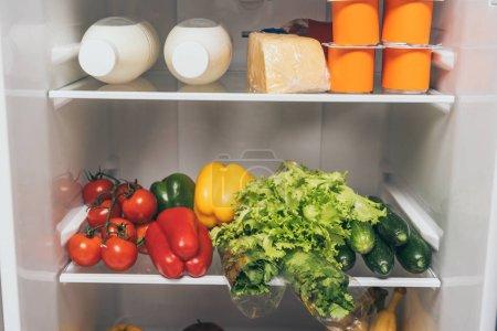 Photo pour Réfrigérateur ouvert plein d'aliments frais sur les tablettes - image libre de droit