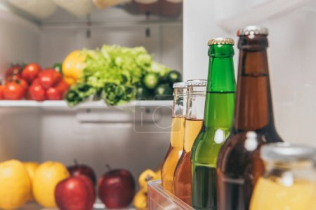 selective focus of bottles of beer on fridge door near fresh food on shelves