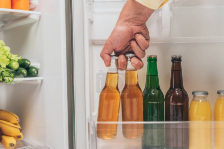 Photo for Cropped view of man taking bottles of beer out from open fridge with fresh food on shelves - Royalty Free Image