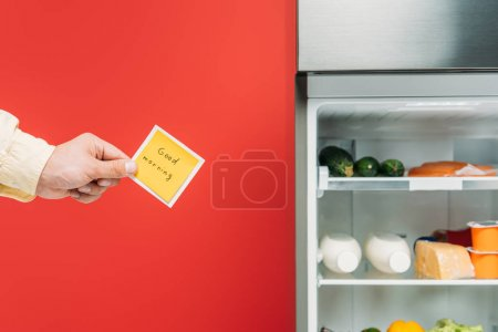 Photo for Cropped view of man holding sticky note with good morning lettering near open fridge with fresh food on shelves isolated on red - Royalty Free Image