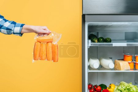 Photo pour Cropped view of woman holding carrots in vacuum package near open fridge with fresh food on shelves isolated on yellow - image libre de droit