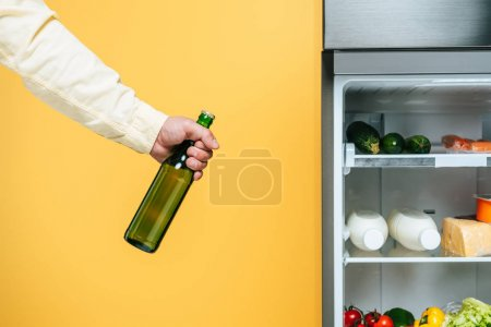 Photo pour Cropped view of man holding yogurt near open fridge with fresh food on shelves isolated on yellow - image libre de droit