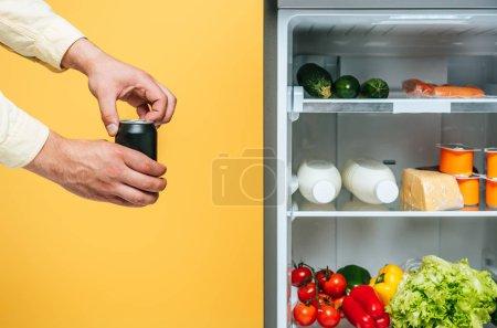 Photo pour Vue en coupe de l'homme ouvrant la boîte de conserve avec de la soude près du réfrigérateur ouvert avec des aliments frais sur les tablettes Isolé Sur jaune - image libre de droit