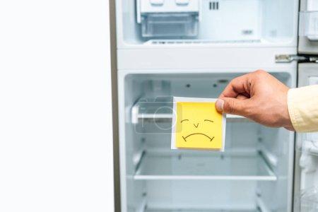 Photo pour Vue recadrée de l'homme tenant triste souriant près du réfrigérateur ouvert vide isolé sur blanc - image libre de droit